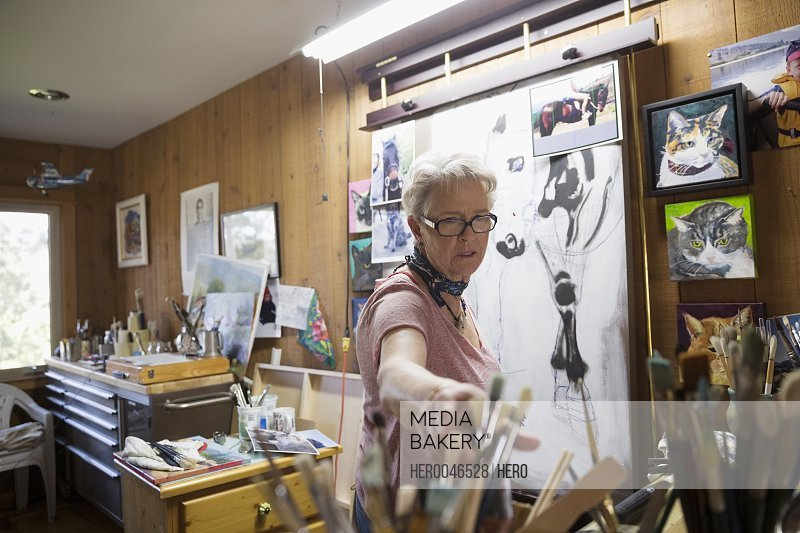Senior woman artist painting in art studio