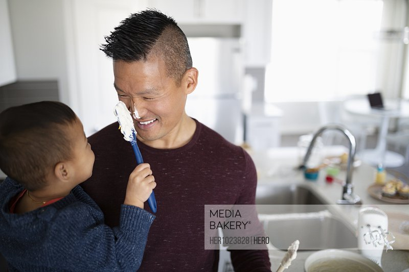 Playful toddler son wiping frosting on father�s nose