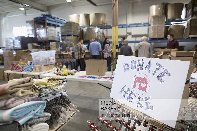 Donate here sign with volunteers in background sorting and boxing toys for toy drive in warehouse