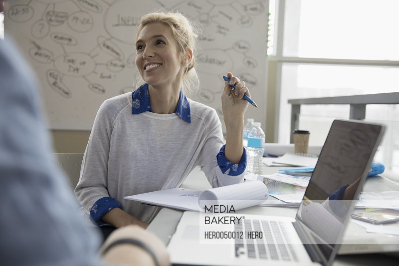 Smiling creative female designer taking notes in office meeting