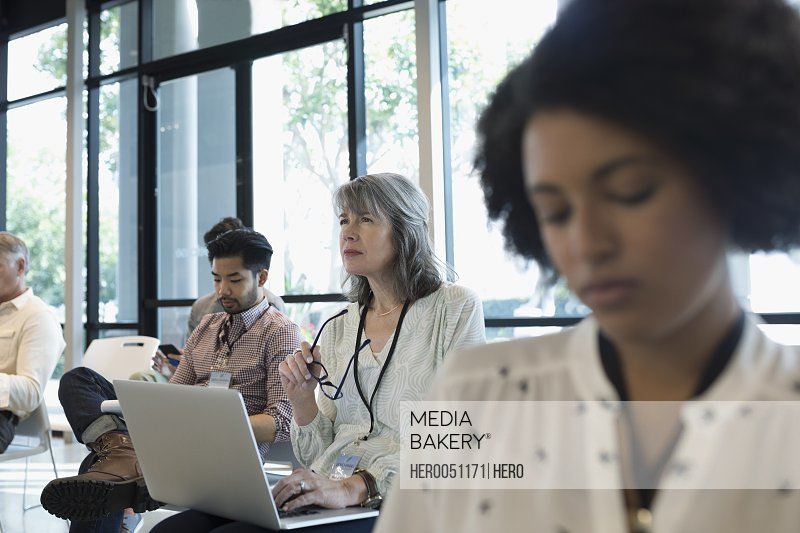 Focused businesswoman with laptop listening in conference audience