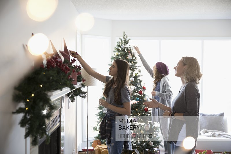Mother And Daughters Decorating Christmas Tree Hanging Garland On Fireplace Mantle In Living Room