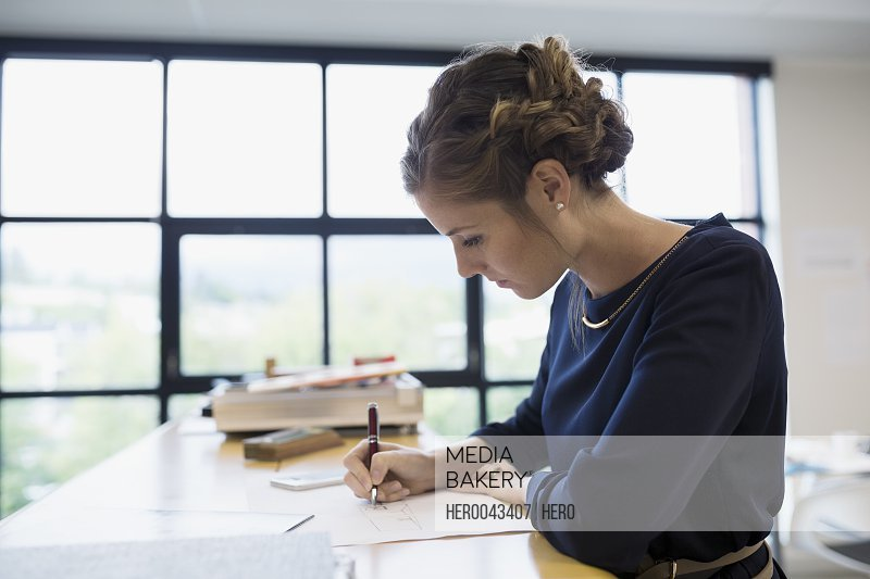 Focused female architect working at table in office