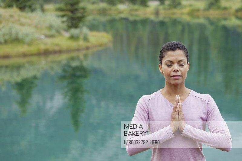 African American woman doing yoga pose by the lake
