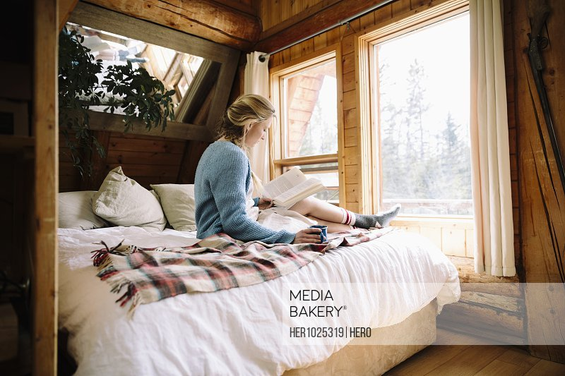 Woman relaxing and reading on cabin bed