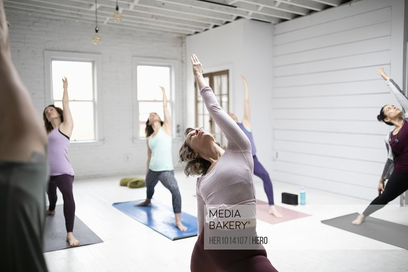 Women practicing yoga reverse warrior pose in yoga class