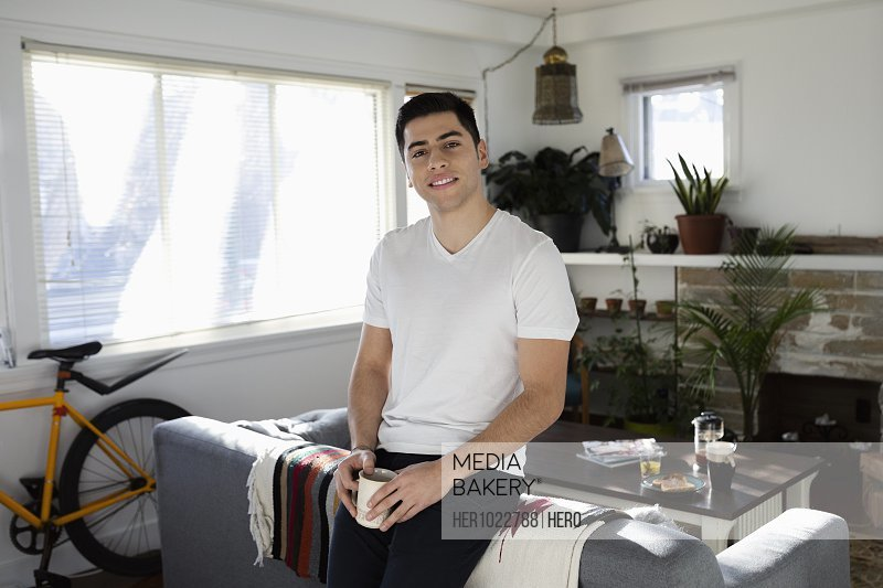 Portrait confident young Latinx man drinking coffee in living room