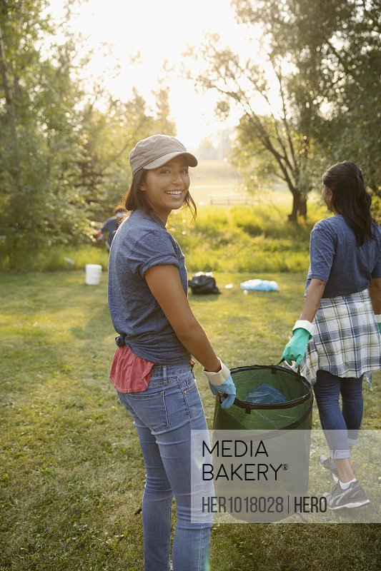 Portrait smiling teenage girl volunteering, cleaning up garbage in park with mother