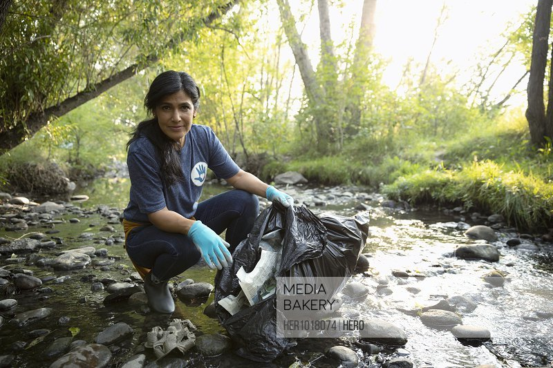 Portrait confident woman volunteering, cleaning up garbage in stream
