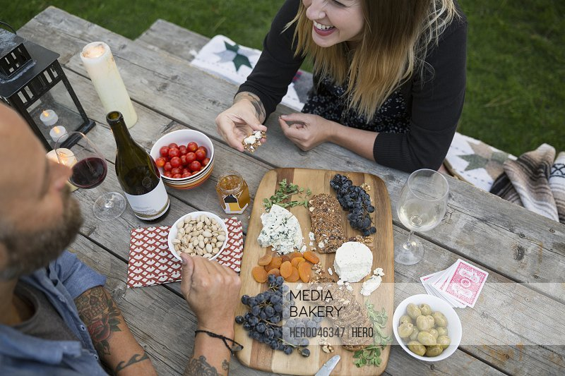 Couple drinking wine and enjoying cheese at picnic table