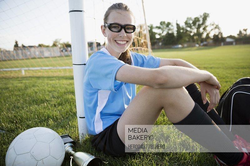 Portrait smiling middle school girl soccer player leaning on goal net post