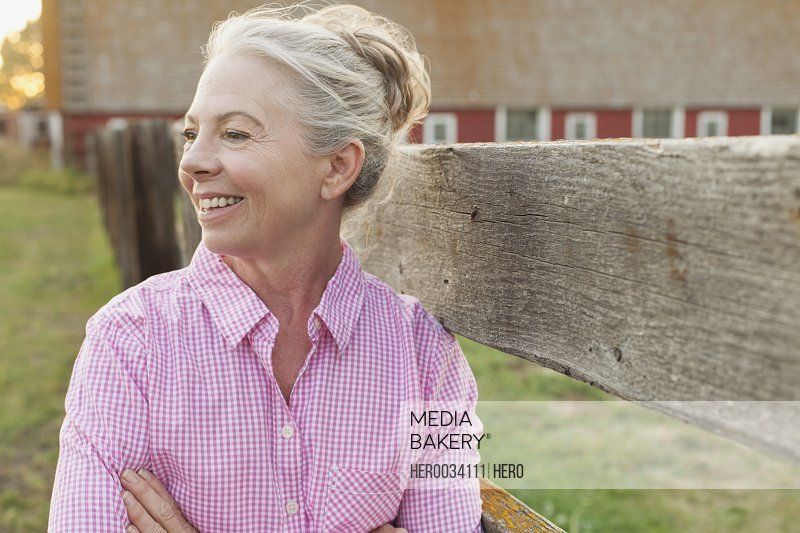 Mature woman standing by fence on rural property.