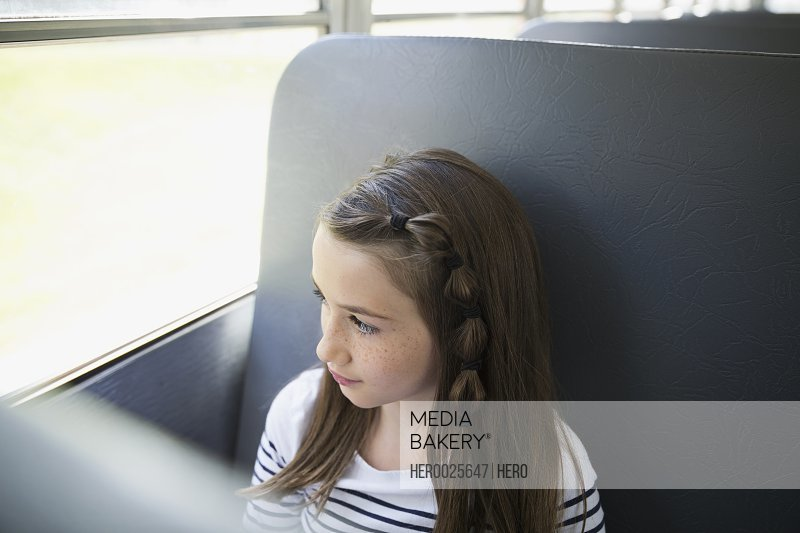 Pensive schoolgirl looking out school bus window