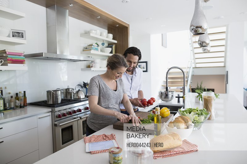 Pregnant couple cooking preparing vegetables in kitchen
