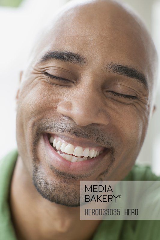 african american man laughing with eyes closed