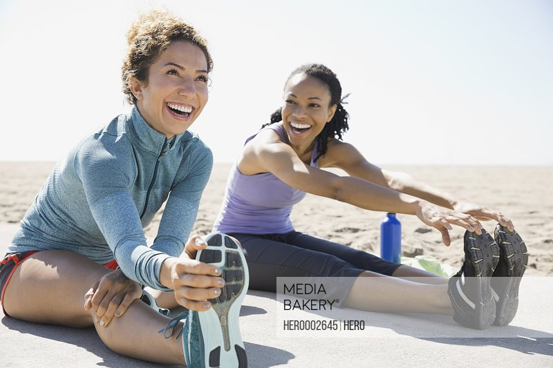 Active women stretching on beach