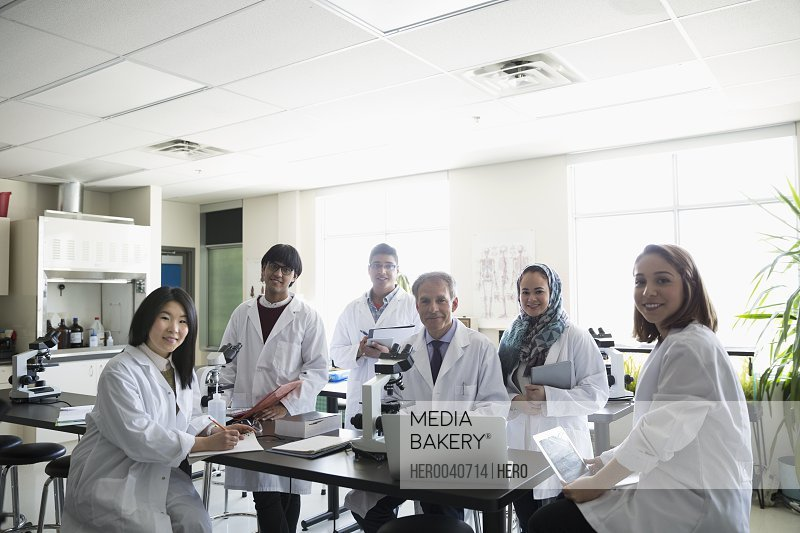 Portrait smiling professor and college students in science laboratory