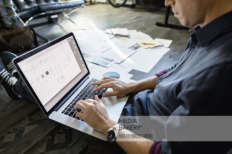 Creative businessman working at laptop on office floor