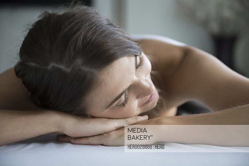 Serene woman laying massage table with eyes closed
