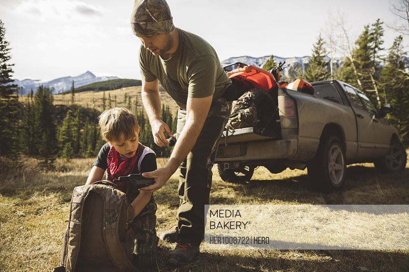 Father and son hunters with walkie-talkie and backpack preparing for hunting