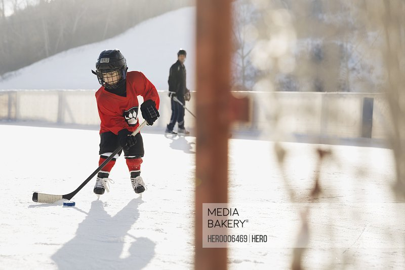 Young ice hockey player practicing on rink