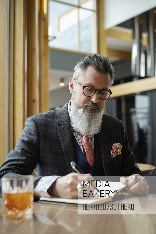Fashionable hipster businessman with beard writing in notebook in bar
