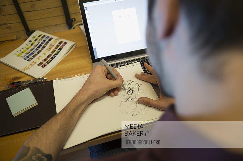 Designer sketching at laptop in office