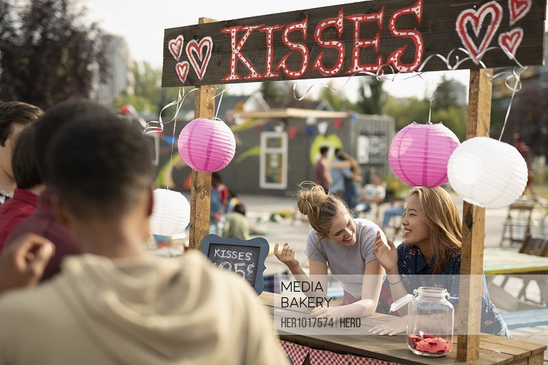Teenage girls at kissing booth in park