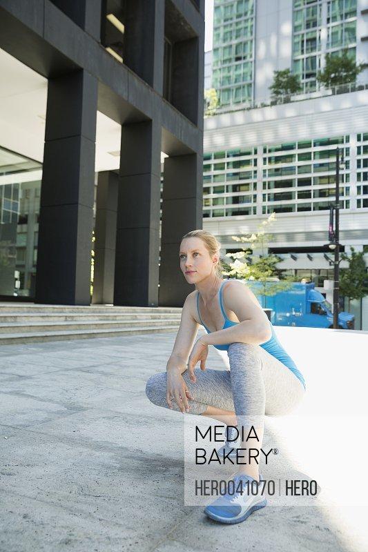 Runner crouching on city sidewalk