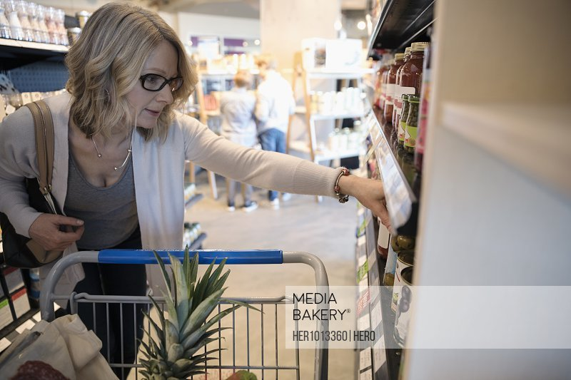Woman grocery shopping, reading label in market