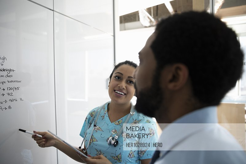 Nurse using whiteboard and smiling towards doctor