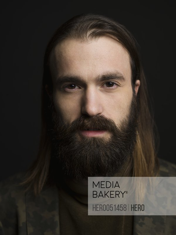Close up portrait serious brunette man with beard against black background