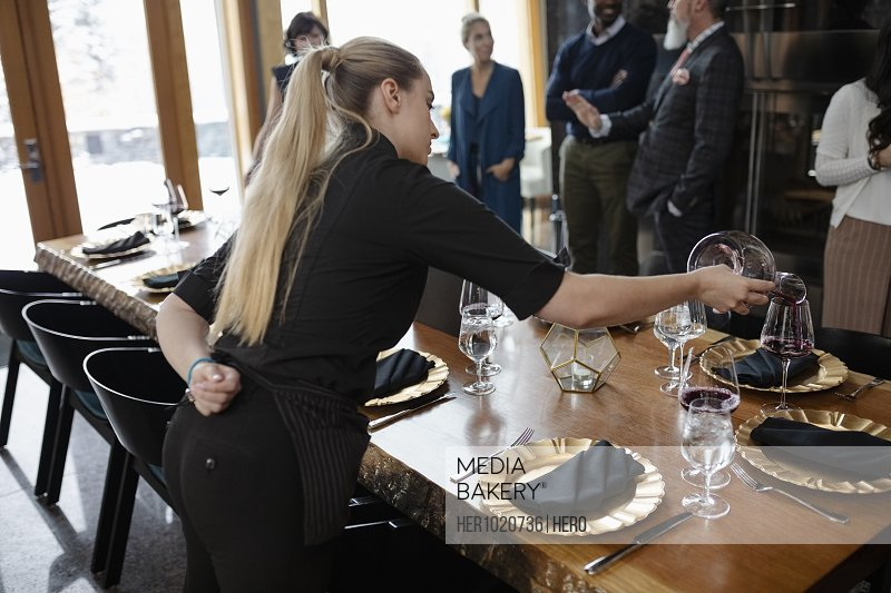 Waitress pouring red wine at restaurant table