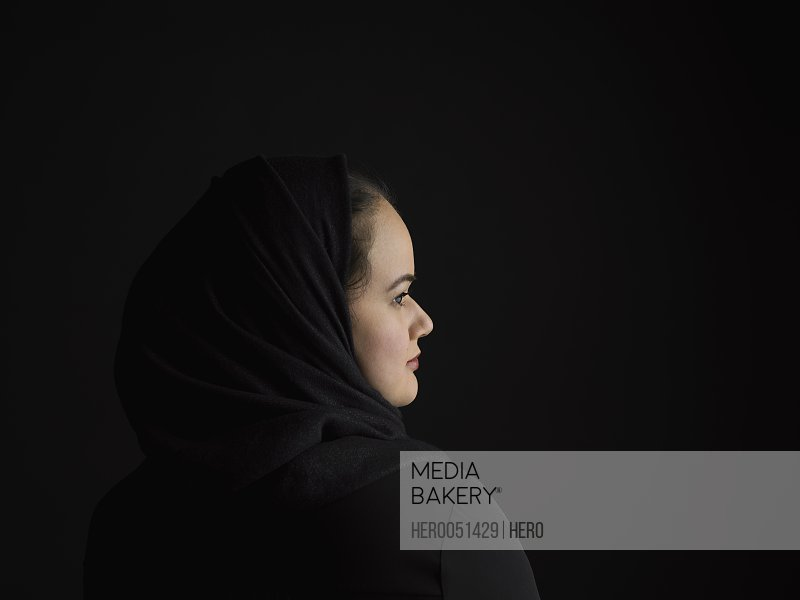 Profile portrait serious Middle Eastern woman wearing black hijab looking away against black background