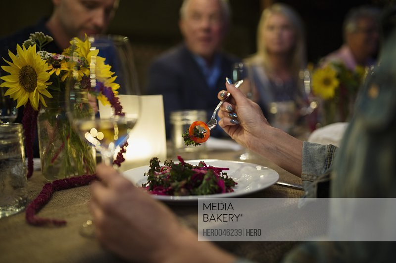 Woman eating at candlelight outdoor dinner party