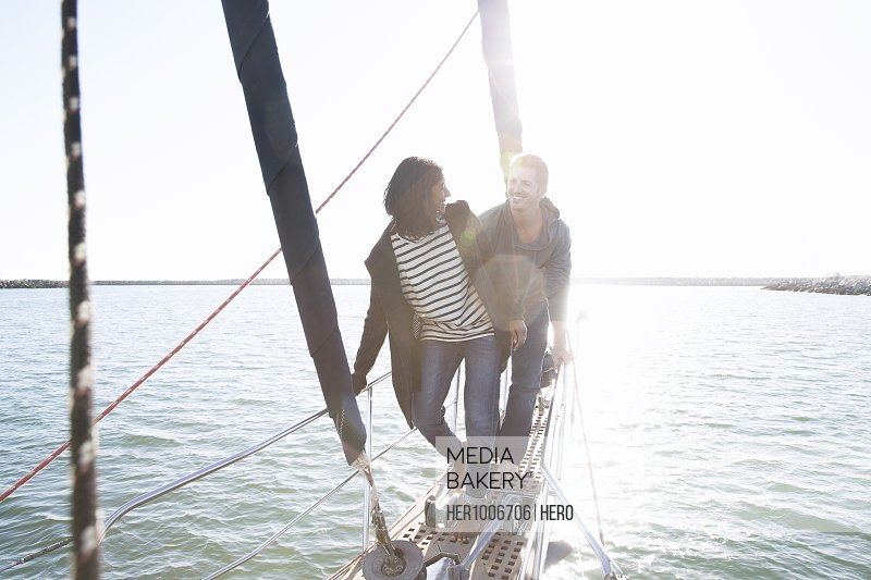 Couple sailing on sunny ocean