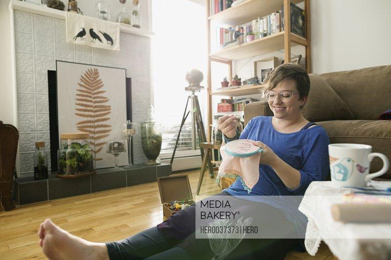 Smiling woman enjoying cross-stitch project living room