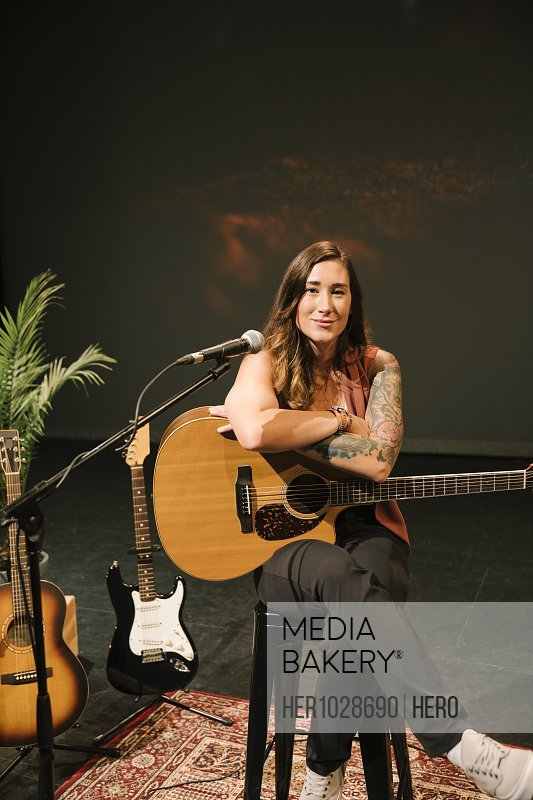 Portrait confident female musician with tattoos holding guitar on stage
