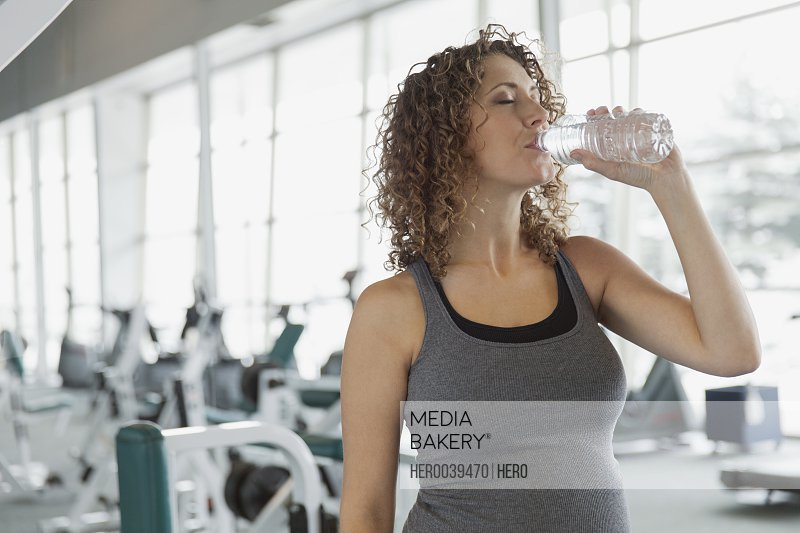 Pregnant woman drinking water at fitness center