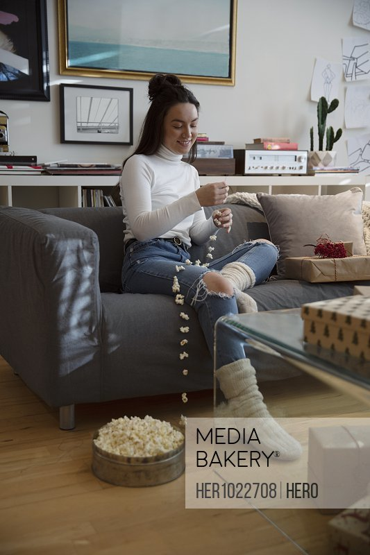 Young woman stringing popcorn Christmas decoration in living room