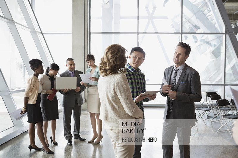 Group of business people with technology talking in office building