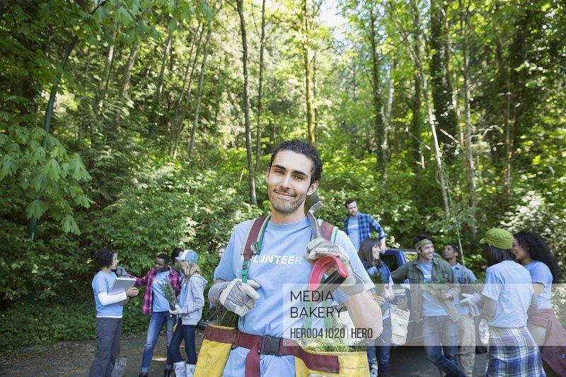 Portrait smiling tree planting volunteer with tree saplings in woods