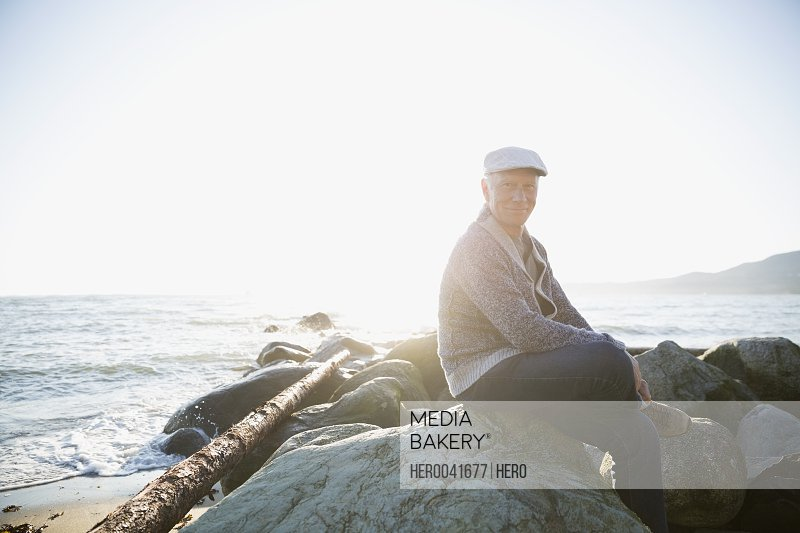 Portrait smiling senior man sitting on sunny beach rocks