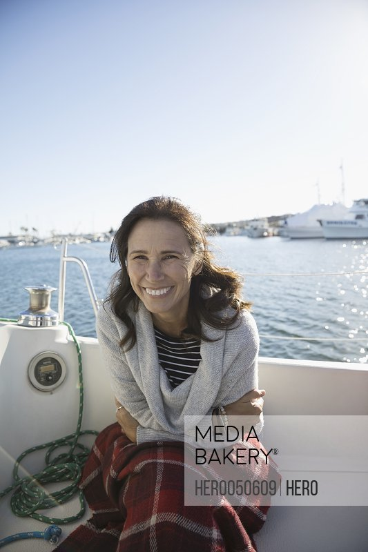 Portrait smiling woman with blanket on sailboat in sunny harbor
