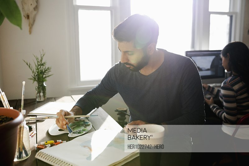 Focused male artist painting in sunny home office