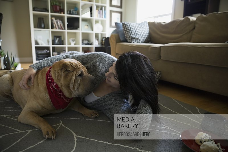 Woman and dog laying face to face floor