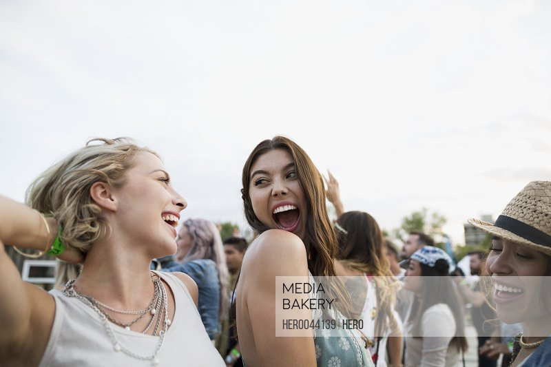 Enthusiastic young women dancing in crowd at summer music festival