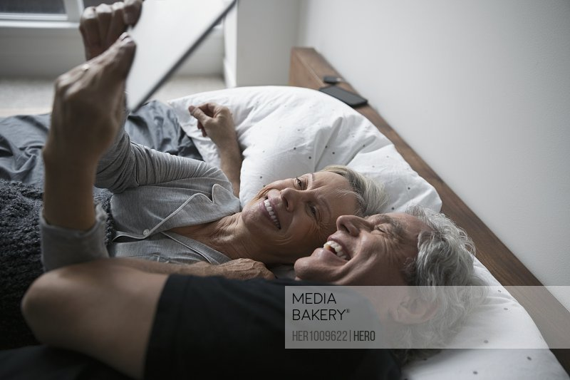 Affectionate, happy senior couple taking selfie with digital tablet, cuddling in bed