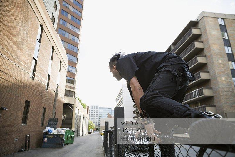Cool man jumping urban fence