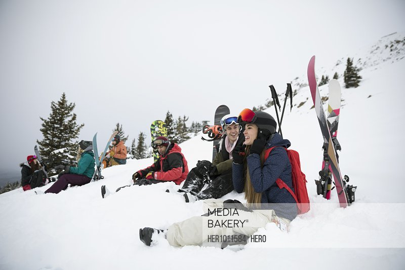 Skier and snowboarder friends resting in snow
